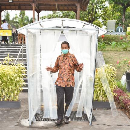 Peserta acara BAST sedang memasuki bilik disinfektan sebagai syarat protocol kesehatan di Rama Shinta Garden Resto, Yogyakarta. (09/10/2020)